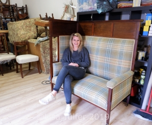 Hannah seated on a re-upholstered settle in her workshop