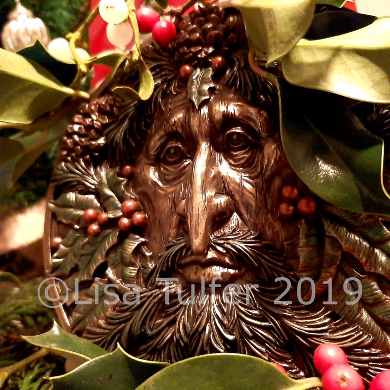 Colour photograph of Yuletide Green Man plaque surrounded by holly.  Image Copyright Lisa Tulfer 2019