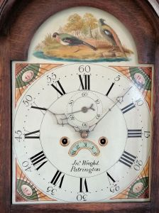 Image of clock face with roman numerals and fanciful birds above.
