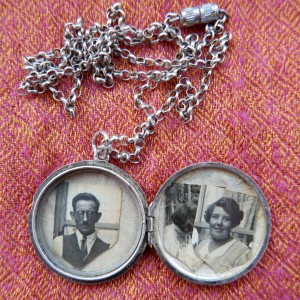Image of a silver locket, with three black and white photographs in it.