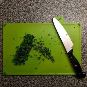 Photograph of a chopping board with chopped herbs and a large kitchen knife.