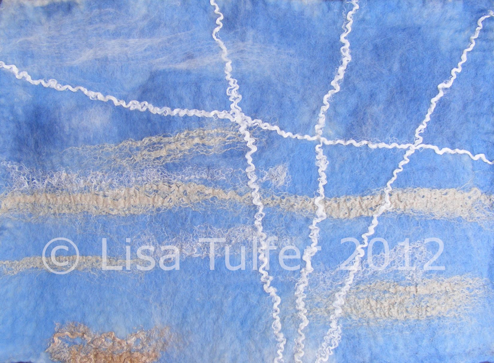 Image of textile art. Skyscape in blue wool with vapour trails and clouds suggested in white and oyster silk. Image and art copyright Lisa Tulfer 2012.