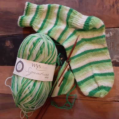 Image of a hand knitted sock, with a second just begun, and a ball of yarn, in stripes of three shades of green.