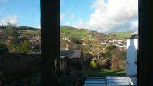 View from window, showing rooftops and distant grassy hills.