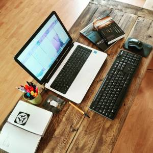 Picture of a desk with laptop, keyboard, diary, pens and books.
