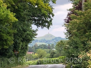 Photograph of Glastonbury Tor, with a road in the foreground and trees framing the view.