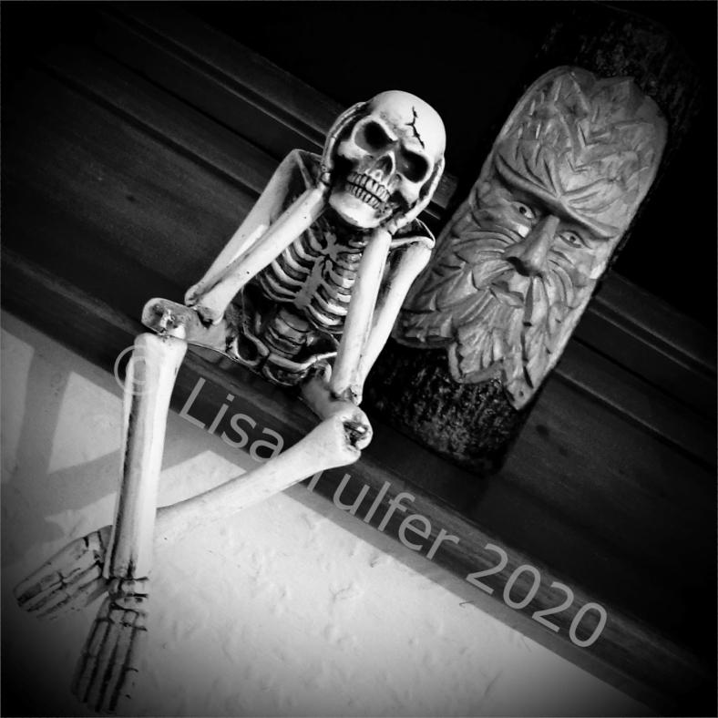 Black and white image of a skeleton ornament and a Green Man carving.