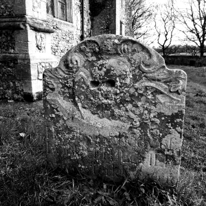 Black and white photograph of an old headstone, carved with a winged skull at Felbrigg Hall (National Trust) Norfolk. Copyright Lisa Tulfer 2020